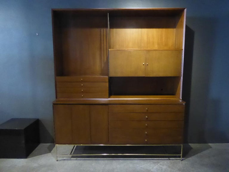 A mahogany and brass credenza / wall unit designed by Paul McCobb for his Irwin collection produced by Calvin Furniture, circa 1950s. The wall unit has a combination of drawers and cabinets with the top section resting on the lower. The original