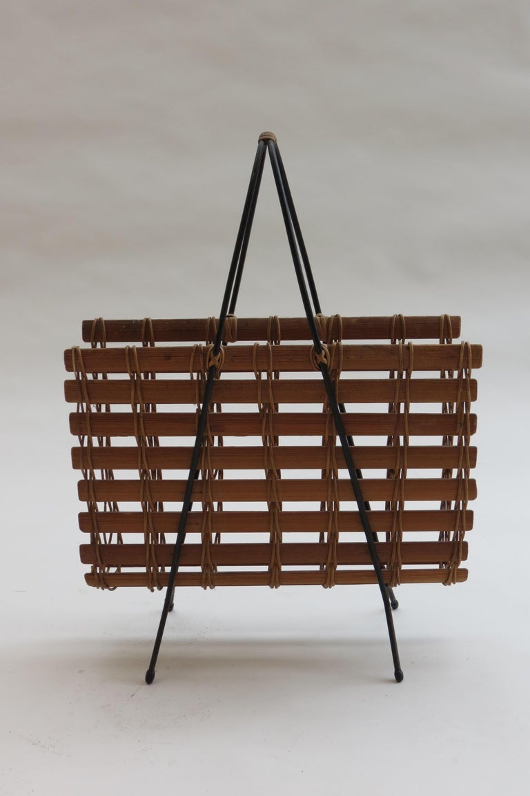 1950s stylish magazine rack made from pine shaped slats, held with rattan and a black painted steel frame with rubber feet.