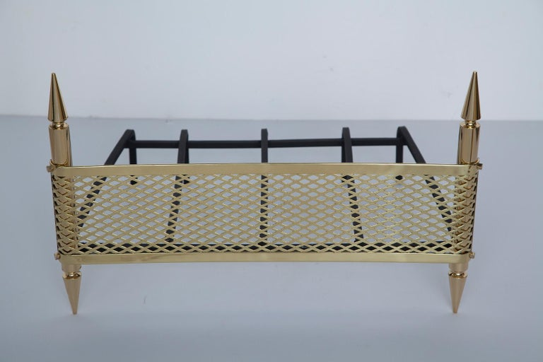 Glamorous 1950s Italian fireplace grate in solid polished brass and wrought iron with Stilnovo maker's mark stamped into brass. Professionally polished.