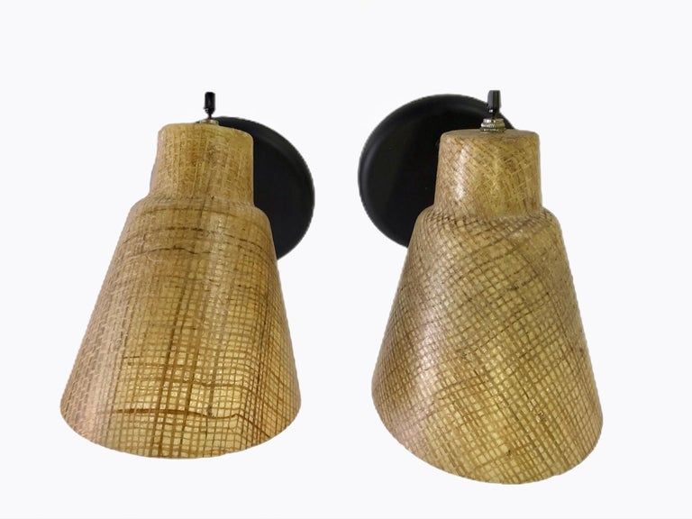 1950s styling in cone shaped sconces of acrylic encasing Raffia. Fully adjustable, they have been rewired and have new black wall plates and turn toggle switches on top.  Measurements: Shade 7 1/2 inches long x 5 1/2 inch opening.