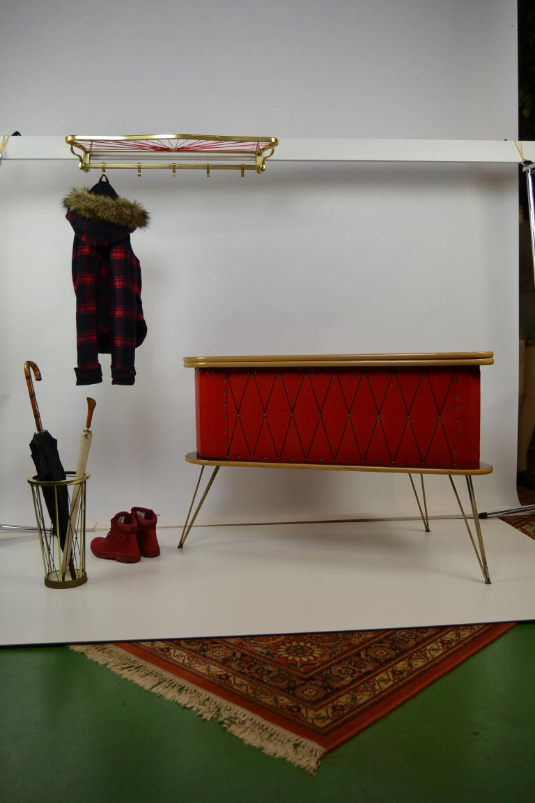 1950s red storage cabinet, home bar, counter, small hall cabinet, shop counter, side table. Wooden cabinet covered with red patent leather, copper details and a black movable top. It has a triangular - rounded shape and can be locked with a
