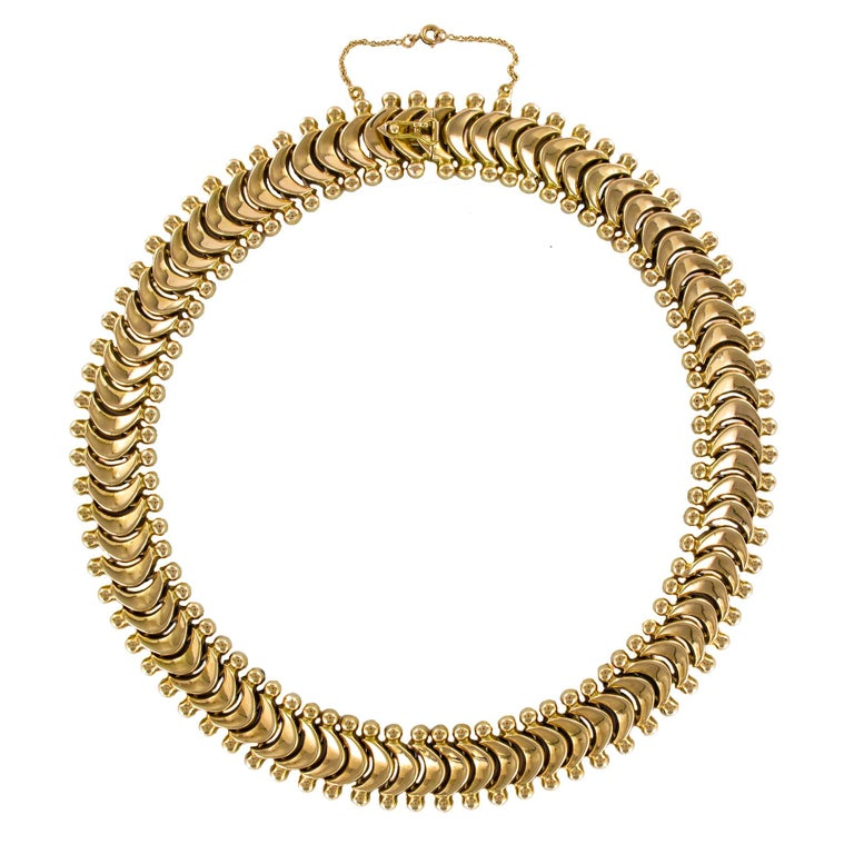 Necklace in 18 karats yellow gold, owl hallmark. This retro necklace is made of crescent moon hinged together and bordered on either side by a gold pearl. The clasp is ratchet with a safety