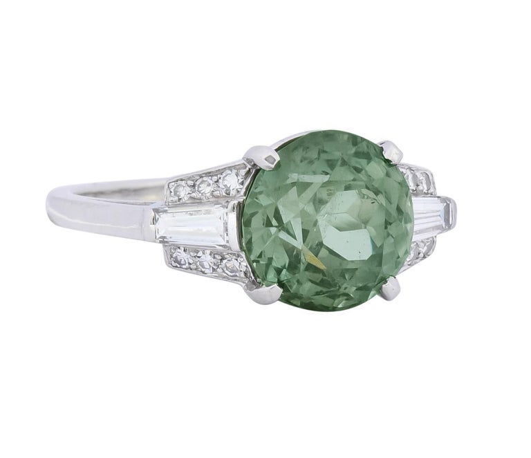 Basket cathedral style ring centering a round cut alexandrite weighing 5.05 carats, transparent and a striking yellowish-green in daylight  Alexandrite color changes to a light grayish-purple when exposed to incandescent light  Flanked by two bar