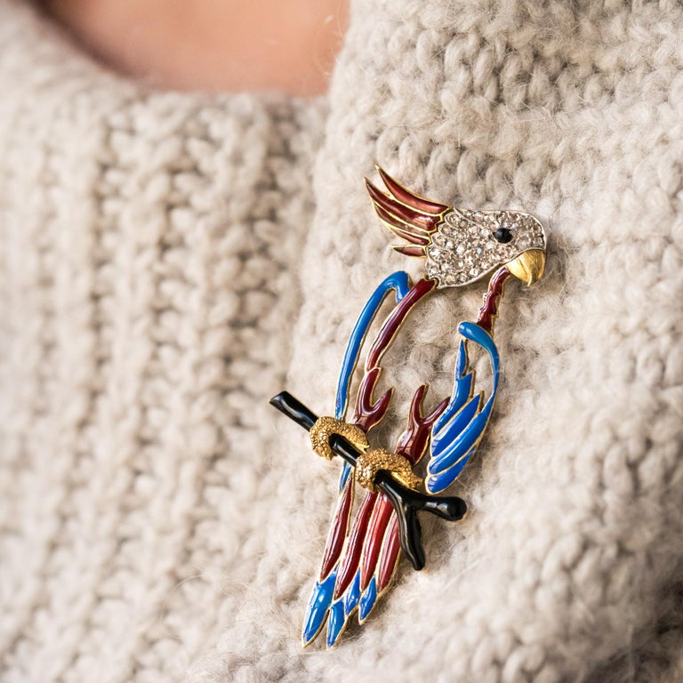 Brooch in 18 karats yellow gold, owl hallmark. This incredible retro brooch represents a parrot whose body is pierced and enamelled blue and red. The bird is resting on a black enamelled gold branch. His head is set with rose-cut diamonds and red