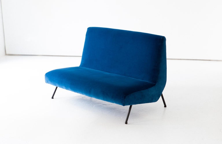 Mid-Century Modern sofa, designed and produced in Italy during the 1950s.  The upholstery is new with high quality 100% cotton blue velvet, we have also worked on the iron legs with new black enamel. We consider that the seat is very