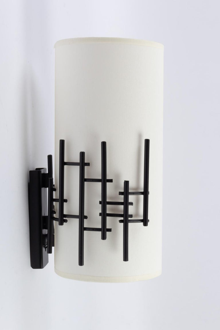 Pair of 1950s wall lights by Rispal, French lights editor in the midcentury. Each sconces features a cylindrical lampshade which is held by a graphical wrought iron random grid. One bulb per sconce.