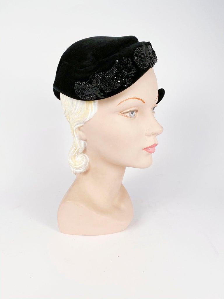 1950s Roos Bros. Black Velvet Hat featuring a black beaded and sequin appliqué to accentuate this hat's asymetrical shape. The body of the hat was made in France and it has an interior comb to reenforce this hat to the head.