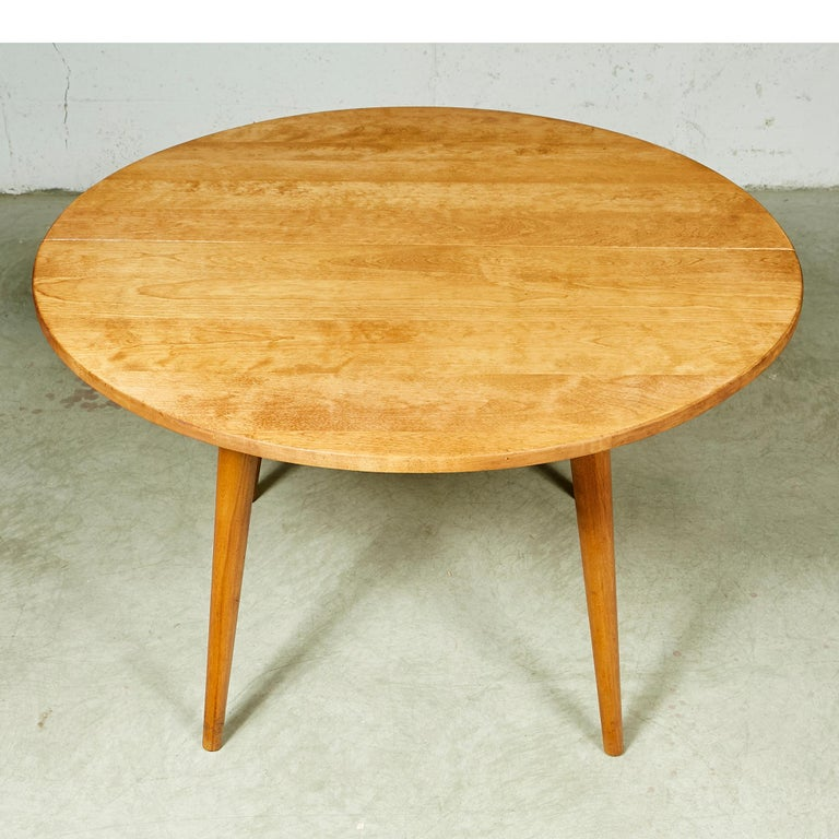 Vintage round maple wood dining table in newly refinished condition with round legs. No maker's mark.