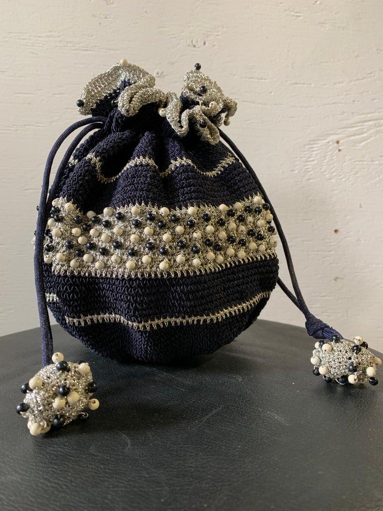 1950s Round Navy & Silver Metallic Crochet Drawstring Summer Handbag W/ Wooden Beading. Resin bottom and ball- shaped fobs at drawstring ends.