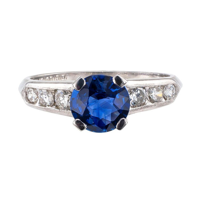 Sapphire and diamond platinum engagement ring circa 1950.  DETAILS: GEMSTONES:  one round, faceted blue sapphire weighing approximately 1.0 carat.  DIAMONDS:  six graduating, round brilliant-cut diamonds totaling approximately 0.32 carat, H – I