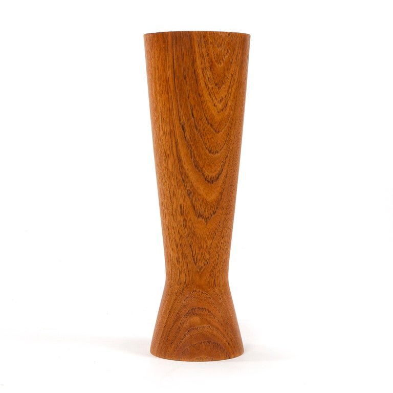 A turned teak vase with a cinched waist.