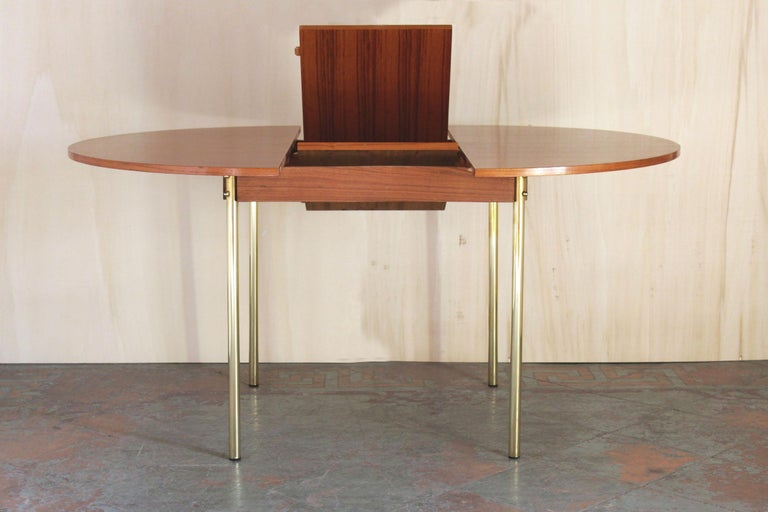 A 1950s round shaped Scandinavian dining table with solid teak top and brass structure. Openable tabletop by the middle in order to reach 6 - 8 seats (please check pictures). In very good conditions with only few small signs of time. TOP: Measures