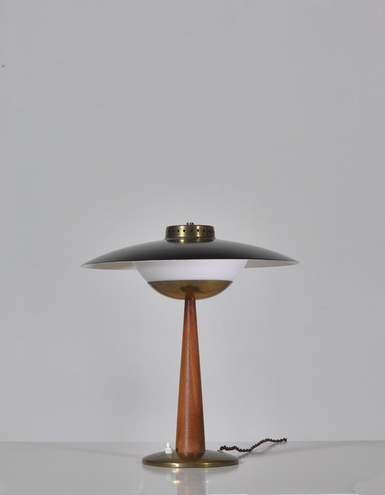 Amazing vintage table lamp made in Scandinavia in the 1950s in the style of Hans Bergström, Svend Aage Holm Sørensen etc. The lamp is produced in high quality materials such as Bangkok teakwood, opal glass and solid brass. It features beautiful and
