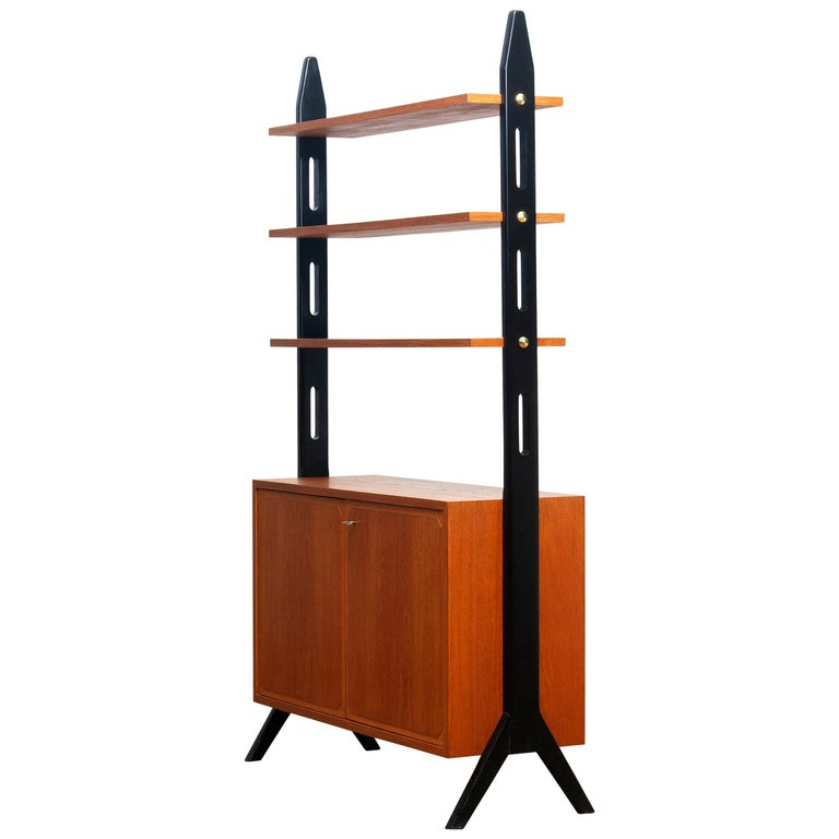 Beautiful Swedish bookcase / room divider / shelf's made in teak from the 1950s. Two folding doors, with a lock, inside the cabinet is a shelf that can be adjusted in two positions. The three top shelf's are placed in a fixed position. Overall