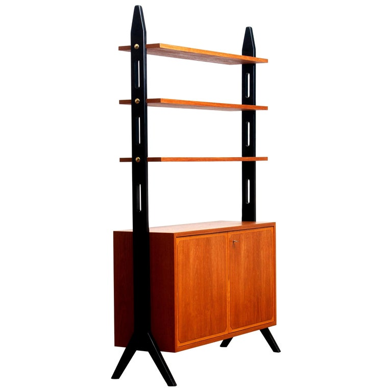 Beautiful Swedish bookcase or room divider or shelf's made in teak from the 1950s. Two folding doors, with a lock, inside the cabinet is a shelf that can be adjusted in two positions. The three top shelf's are placed in a fixed position. Overall
