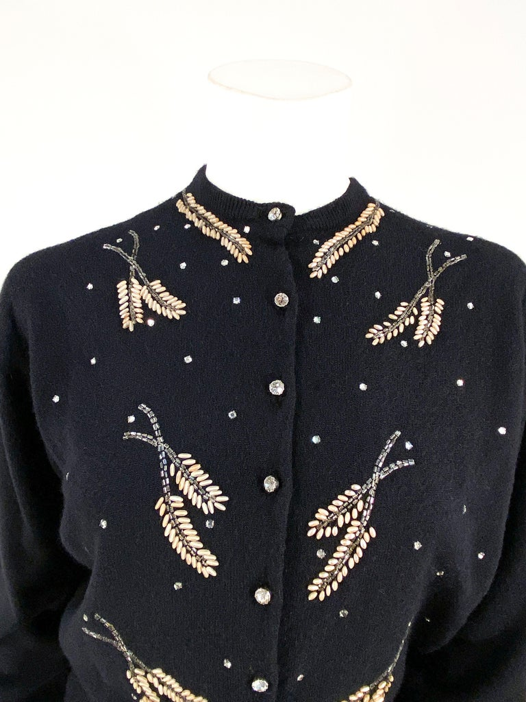1950s Schiaparelli black cashmere cardigan sweater with large rhinestone studding and beadwork set in leaf patterns. The front has large rhinestone buttons on the front closure, the cuff ribbing is elongated to be worn in a rolled-up cuff fashion