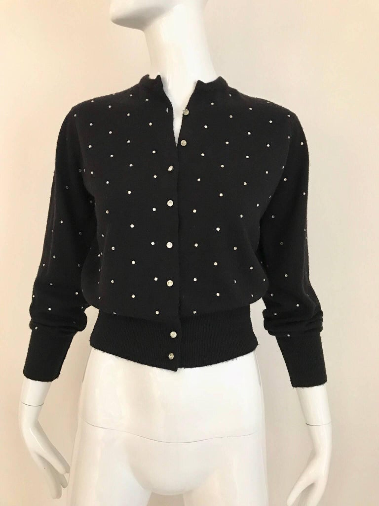 Elegant Vintage black sweater from 1950's by Schiaparelli in cashmere with a sparkle of rhinestones. The waist band further defines the feminine shape! Size: Small (4 or 6)  **missing 1 button on the fold