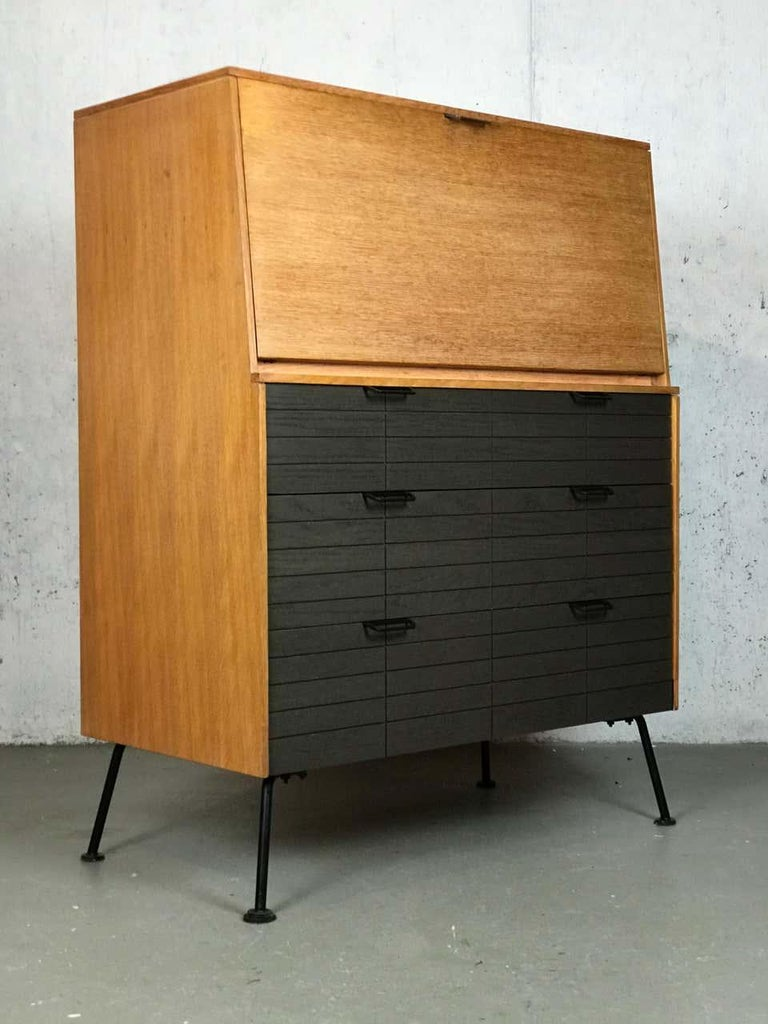Excellent example of Minimalist 1950s design with an array of contrasting materials; wood, paint, and patinated steel legs, that show off a young Raymond Loewy's prolific future in design. This secretary cabinet retains the original finish that is