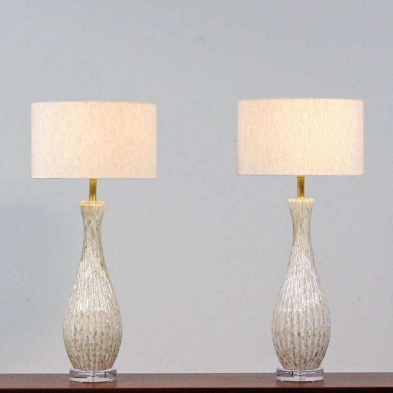 Impressive, 1950s pair of Murano glass lamps featuring a wonderful gold flecking and encased bubble (bullicante) technique on a white background by Alfredo Barbini. These beautiful lamps have been newly rewired. The brass hardware has been cleaned
