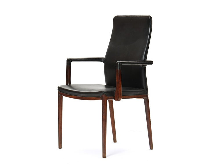A rare and beautiful set of 8 sculptural rosewood dining chairs retaining their original black leather; there are six side and two armchairs in the set. Designed by Helge Vestergaard Jensen, and made by cabinetmaker Peder Pedersen.