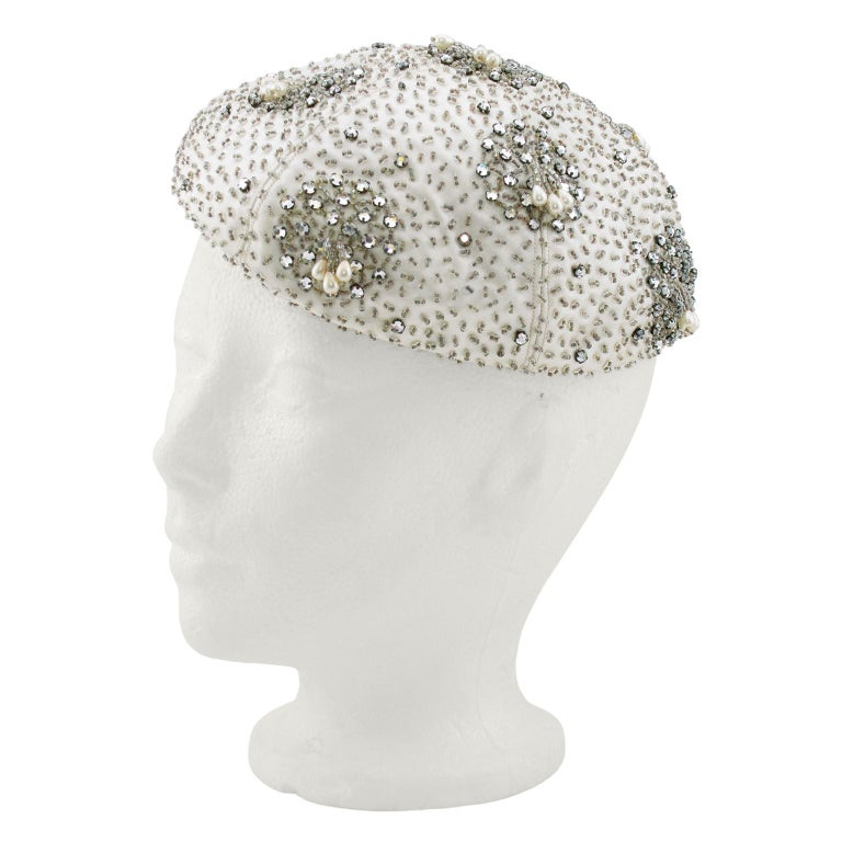 Fabulous 1950s silver beret. Embellished off-white satin fabric  with small clear beads and silver rhinestones. Small beaded tassels with teardrop shaped pearls. Contrasting interior magenta grosgrain ribbon. 22.5