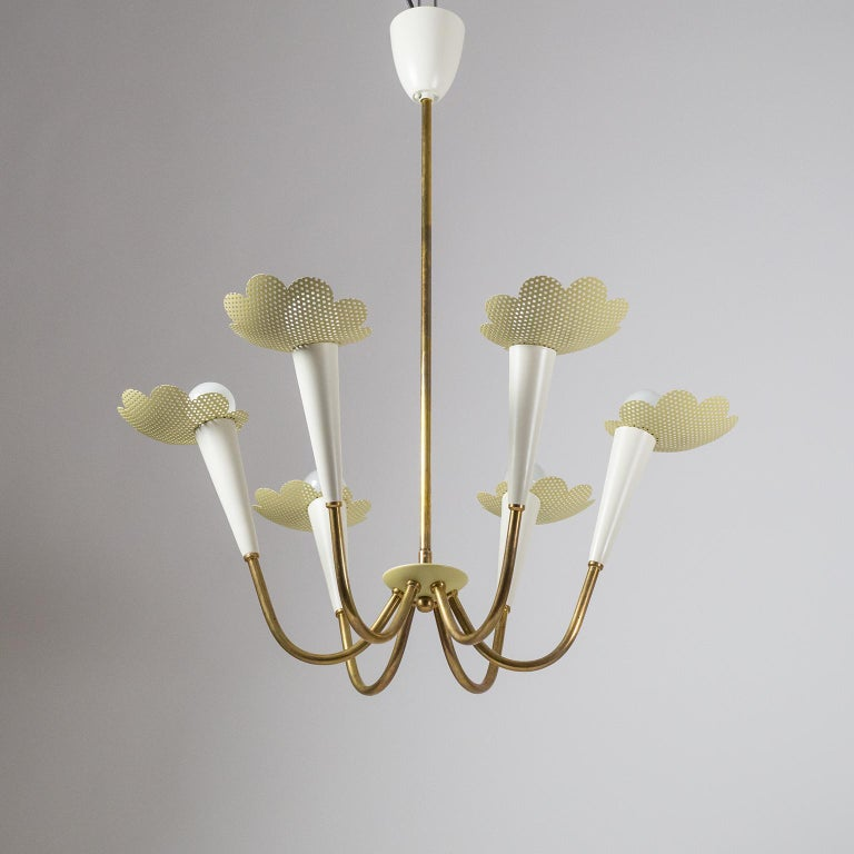 Delightful modernist chandelier from the 1950s. Six brass arms, each with an off-white lacquered socket cover and a pastel-mustard colored pierced floral shade. The brass parts have a lovely vintage patina, while the lacquered parts have been