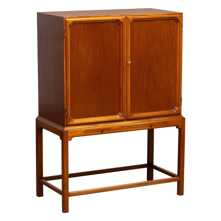 Beautiful dry bar / cabinet in mahogany on tall slim legs made in Sweden, 1950s. Equipped with two lockable doors with behind four drawers and shelves. The shelves and rear are decorated with glass mirrors. Also an extendable shelf at the front