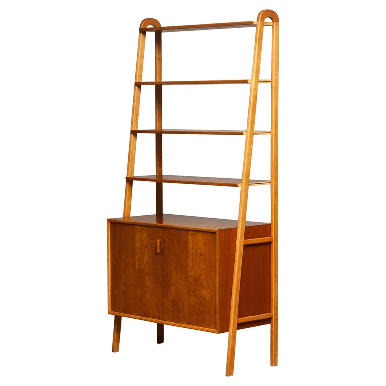 Beautiful and typical Swedish slim bookcase / shelfs cabinet in teak in combination with beech stands made by Brantorps, Sweden. This cabinet consists four shelfs in which three are adjustable. The top shelf is fixed. There is also an adjustable /
