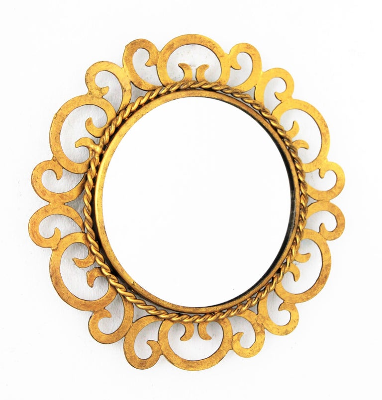 Lovely handcrafted gilt iron sunburst mirror with alternating scroll motif and gilt finish. Unusual in this small size, Spain, 1950s.
