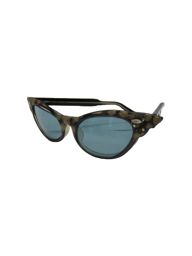 Effortlessly cool sunglasses from the 50s. Featuring a black and brown spotted frame with grey tint lenses which complement the glasses well and provide contrast. Jeweled details can be found on the side of the arms and on the frame's corners