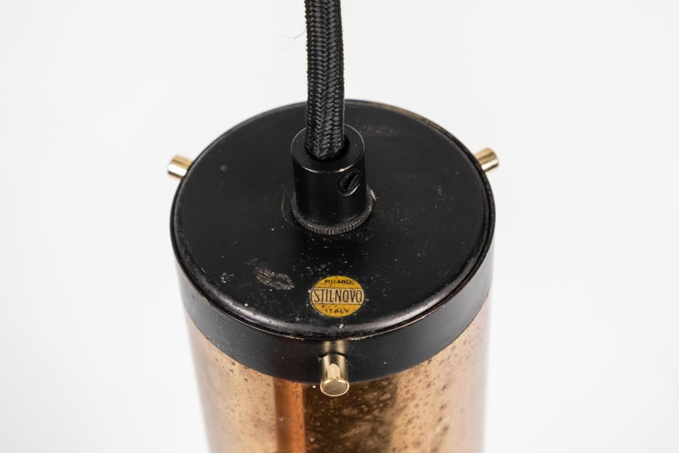1950s Stilnovo cylindrical pendant with yellow label. A quintessentially 1950s Italian design executed in brass and black perforated painted metal with a custom fabricated architectural ceiling canopy for mounting over a standard American J-box. A