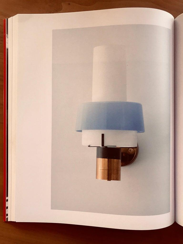 1950s Stilnovo Model 2079/1 brass and glass sconce with original label. Executed in brass, thick opaline glass, red Perspex and retains original Stilnovo label. A sculptural and refined design characteristic of midcentury Italian lighting at its