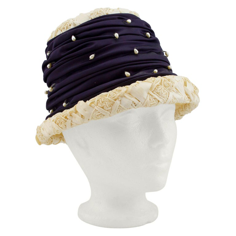 Darling hat from the 1950s. Natural straw with thick large ruched satin band around the crown of the hat, embellished with small teardrop shaped pearls and beads. Small brim. Excellent vintage condition. Average size.