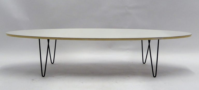 Midcentury classic look with this period Surfboard coffee cocktail table on hairpin Legs. With a elliptical white formica top, white lacquered edge, raised up on four black wrought iron hairpin legs. In very, very good condition with minor flakes