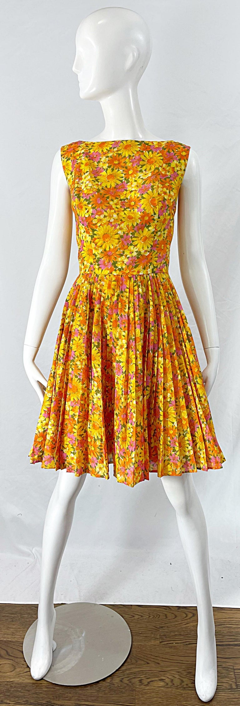 Chic 1950s SUZY PERETTE yellow, orange, pink and green daisy flower print cotton fit n' flare dress ! Features an elegant high neck with a tailored bodice and forgiving full pleated skirt. Full metal zipper up the back with hook-and-eye closure.