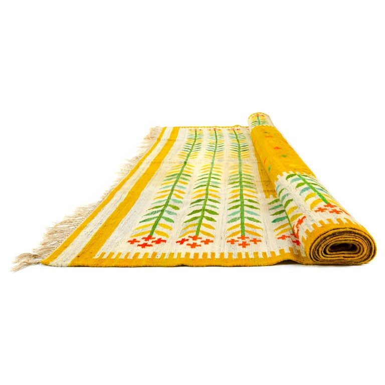 A colorful handwoven wool rug with a bright botanical motif.