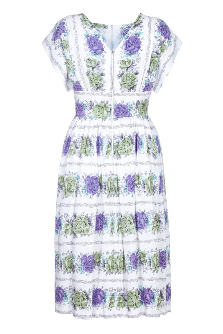 This lovely 1950s white cotton rose print dress is skilfully made and in pristine vintage condition. The fine printed cotton is soft to touch and of notable quality, featuring a pretty linear rose design in pale green, violet and turquoise which