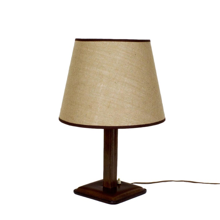 Table lamp, wood covered with leather, light thread sewing, jute lampshade with a brown fabric edging.  Spain, circa 1950.