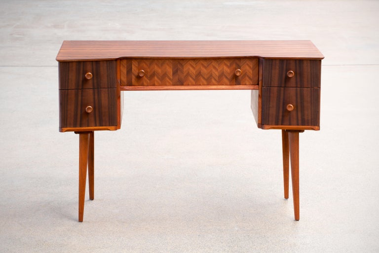 Beautifully designed writing desk in teak and walnut. With a very distinct design this desks every wood surface has been given specific angles such as the tabletop, the unit with drawers as well as the legs. The desk is given a very light and airy