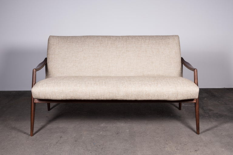 The epitome of Mid-Century Modern refinement. This iconic teak loveseat sofa represents some of the best design and craftsmanship of the era.  Invitingly relaxed and magnificently elegant.  The sculpted teak wood, elegantly darkened with age, is