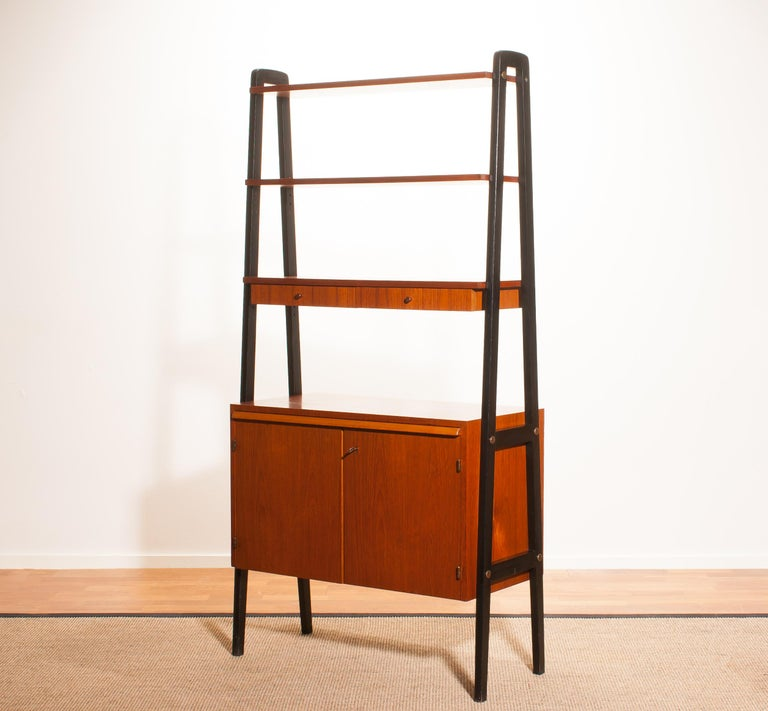 Beautiful cabinet, room divider, bookcase, secretaire in teak with black stands. This cabinet has got two shelves, one shelve with two drawers, two doors and a slidable writing space. It is in a very beautiful condition. Period 1950s Dimensions