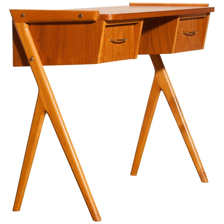 Very beautiful vanity or ladies desk from Sweden The table is made of teak and has two drawers with brass details. It is in a very nice condition. Period, 1950s. Dimensions: H 70 cm, W 84 cm, D 40 cm.
