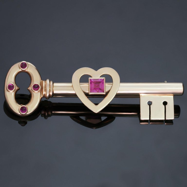 This rare retro Tiffany & Co. brooch features a design of a key with a heart-shaped motif crafted in 14k rose gold and set with 4 round cabochon pink sapphires and one square pink sapphire. Made in United States circa 1950s. Measurements: 0.66