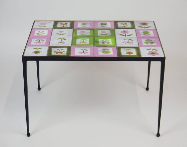 A coffee table with a glazed ceramic tiles top decorated with flowers on a black enameled wrought iron structure. This 1950s coffee table with different colors stylized flowered tiles is in the style of