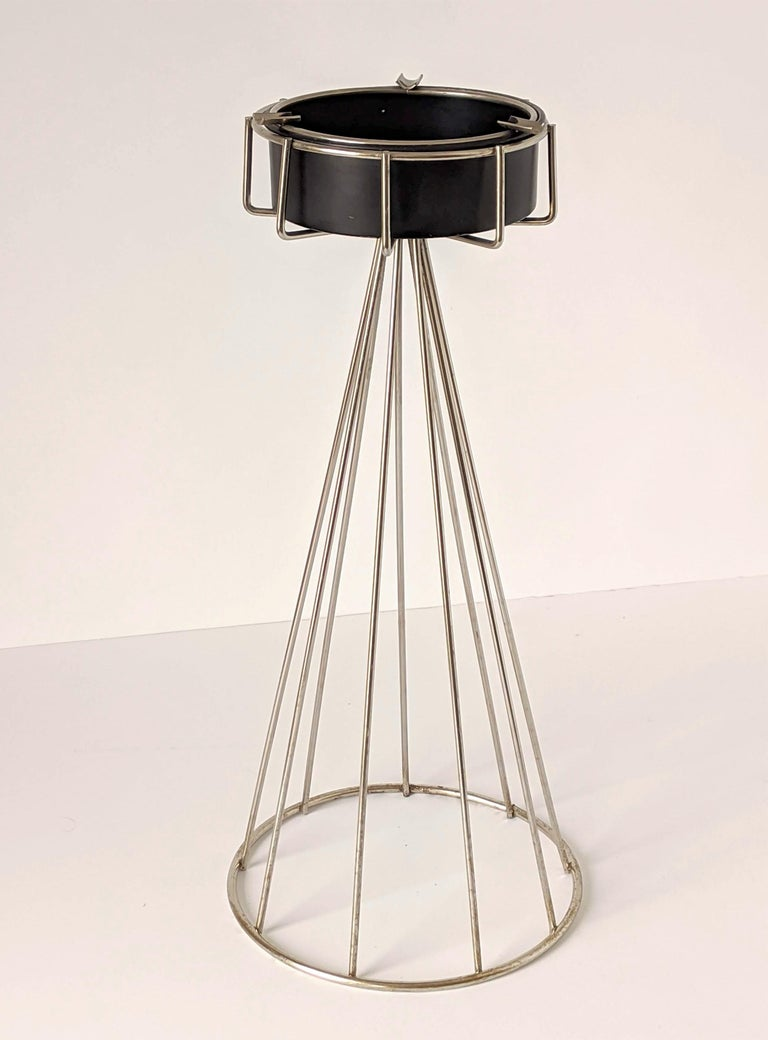 From the wire series an architectural chrome structure with an enameled black semi gloss ashtray.  Measure 20.5 inches high.   Ashtray is 6 in. wide.