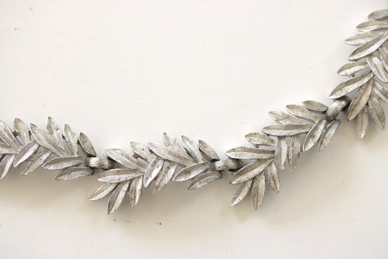 A Vintage articulated brushed silver tone leaf necklace and matching earrings by famed Trifari.  circa 1950s. The delicate appearance of each asymmetrical leaf with a ribbed pattern design has 10 linked panels on the necklace a chain for