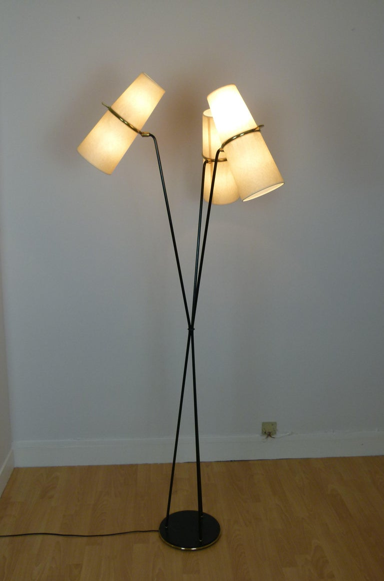 Floor lamp in black lacquered metal and brass, composed of a circular base in black lacquered cast iron, set with a brass ring on which are arranged three lacquered metal sconces, which intertwine in their middle. Each arm has at the end, a brass