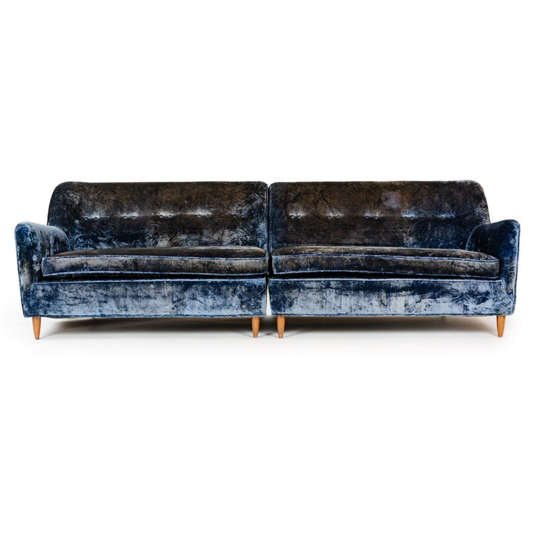 A two-piece tight backed crushed blue velvet sofa retaining original upholstery.