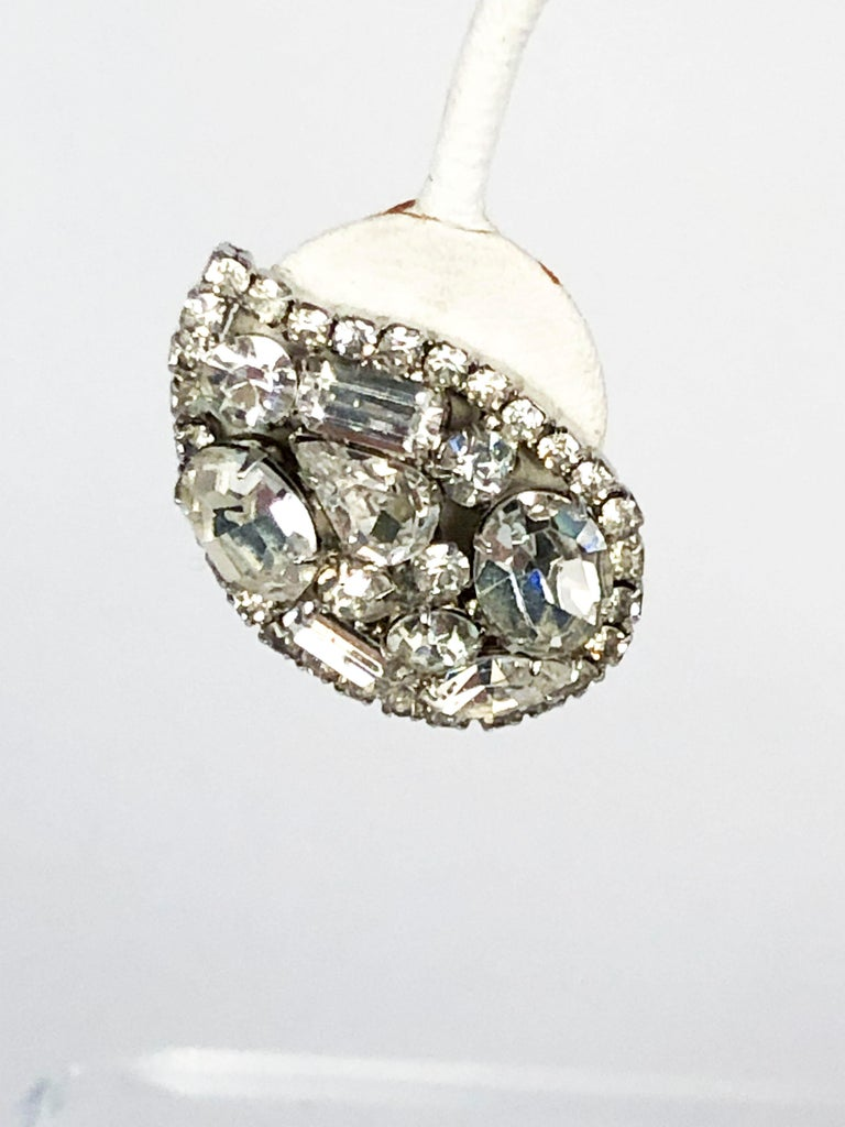 1950s Vendome clip-on earrings with multi-cut/multi-sized clear rhinestones set in a setting metal with a silver wash. The Rhinestones are configured into a teardrop shape to accentuate the shape of the ear. The clips have a screw to adjust the