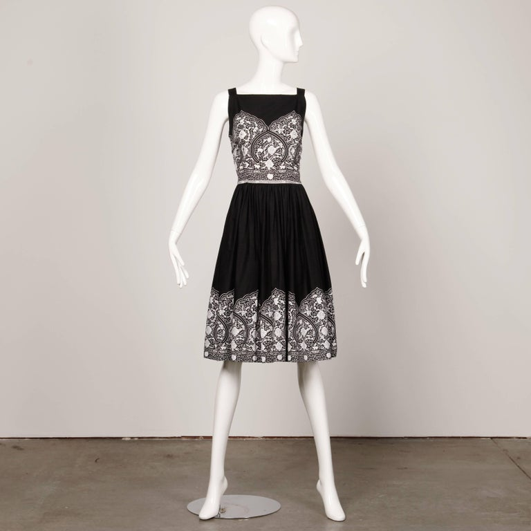 Darling vintage 1950s vintage patio dress in black and white cotton. Prong set rhinestone detail and full skirt. Unlined with side metal zip closure. Fits like a modern size medium. The bust measures 38